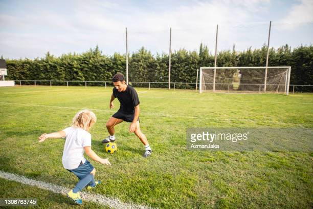 coach dribbling against 6 year old footballer in practice - defender soccer player stock pictures, royalty-free photos & images