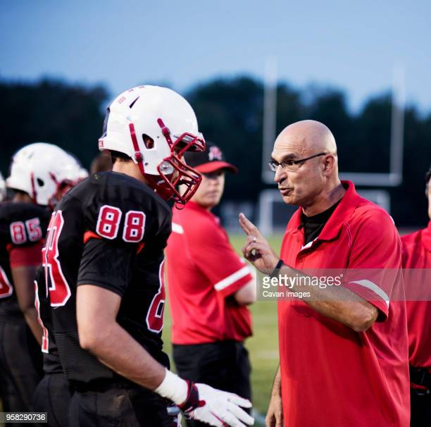 coach explaining american football players on field - high school football stock pictures, royalty-free photos & images
