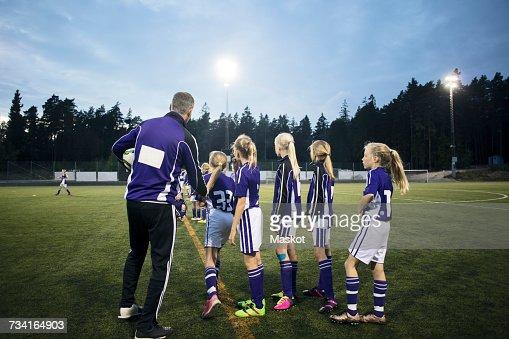 Coach explaining female soccer team on field against sky