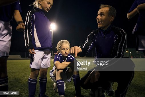 Coach explaining strategy to girls on soccer field at night
