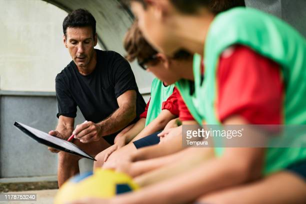 coach explaining the game plan - calcio sport foto e immagini stock