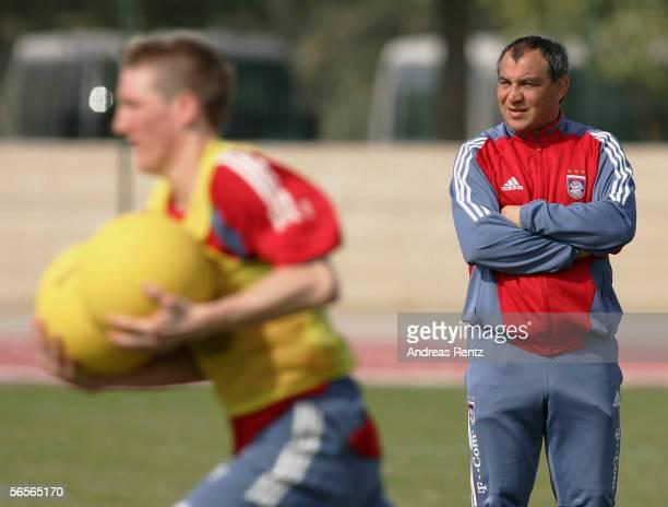 Coach Felix Magath looks on as Bastian Schweinsteiger runs with a medicine ball during the training camp of German Bundesliga club Bayern Munich on...