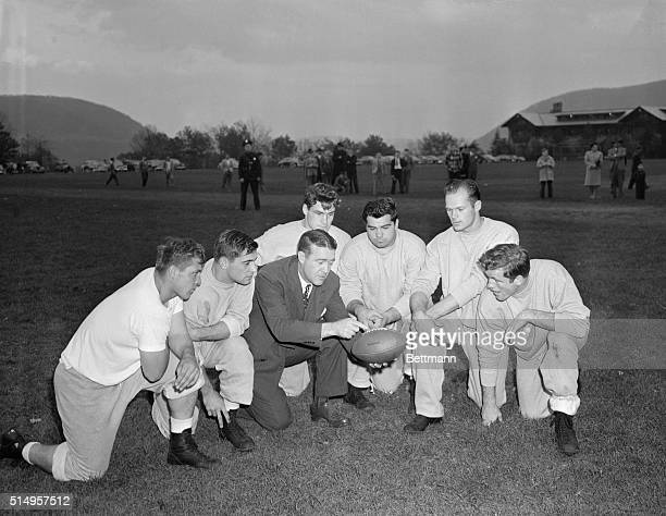 Coach Frank Leahy and his Notre Dame invalids are shown in a huddle during a light workout at Bear Mountain NY in preparation for the allimportant...