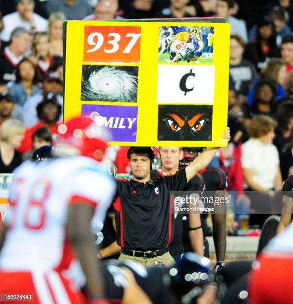 A coach from the Cincinnati Bearcats holds up a play sheet for the offence during a game with the Delaware State Hornets at Nippert Stadium in...