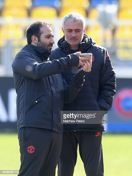Coach Giovanni Cerra of Manchester United shows Manager Jose Mourinho photos of the pitch during a first team training session at Olimp2 on March 8...