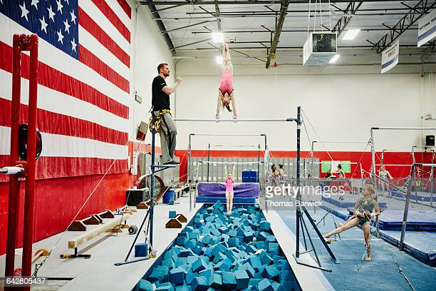Coach giving directions to gymnast on bars