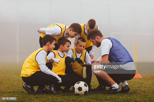 coach giving instruction to his kids soccer team. - coach stock pictures, royalty-free photos & images