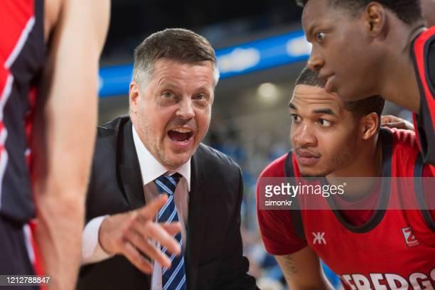 coach die instructies geeft aan basketballers - court hearing stockfoto's en -beelden