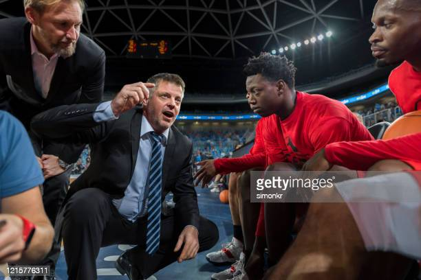 coach giving instructions to basketball team - coach stock pictures, royalty-free photos & images