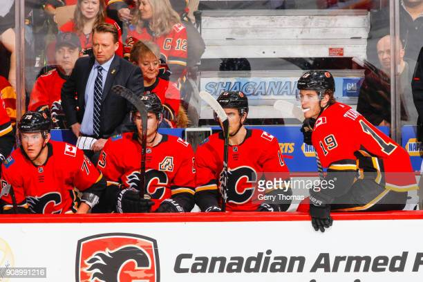 Coach Glen Gulutzan and teammates of the Calgary Flames watch the action in an NHL game on January 22 2018 at the Scotiabank Saddledome in Calgary...