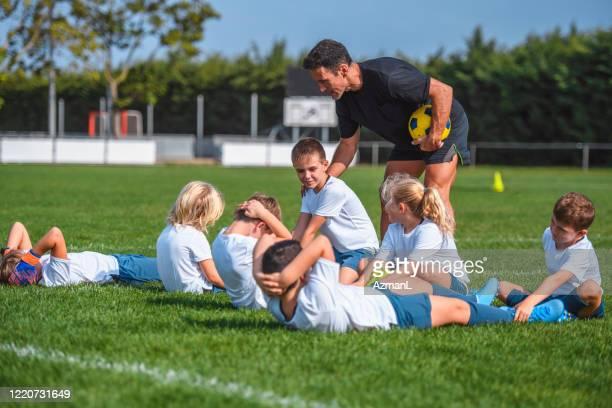 コーチガイディング若いサッカー選手は、座って - さまざまな年齢層 ストックフォトと画像