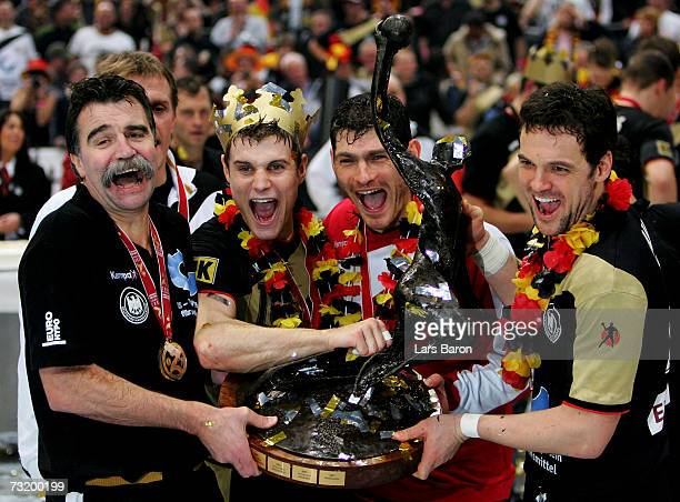 Coach Heiner Brand Michael Kraus goalkeeper Henning Fritz and Markus Baur of Germany celebrate with the cup after winning the IHF World Championship...