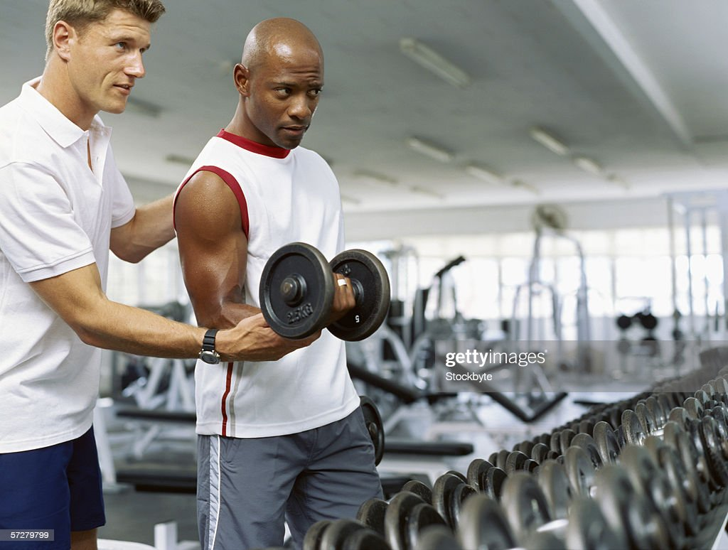 Coach helping a mid adult man exercise with dumbbells : Stock Photo