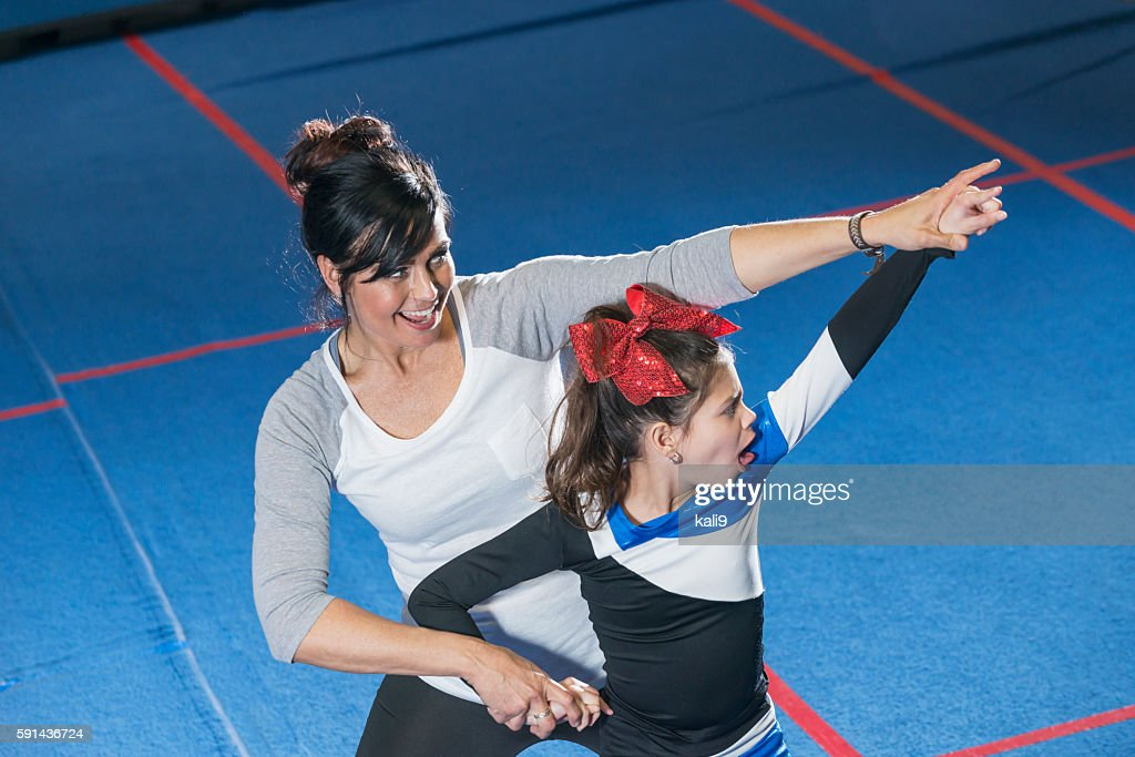 Coach helping autistic girl on cheerleading team : Stock Photo