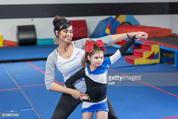 coach helping autistic girl on cheerleading team - cheerleaders stock pictures, royalty-free photos & images
