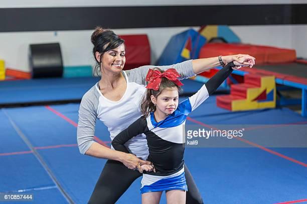Coach helping autistic girl on cheerleading team