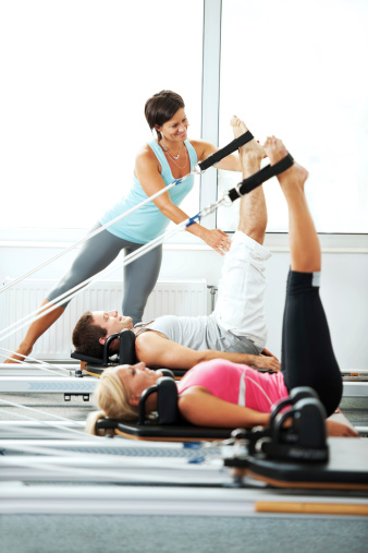 Coach helping people with Pilates exercises. - gettyimageskorea