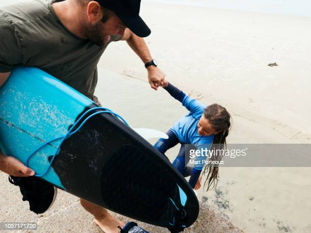 Coach helping young surfer