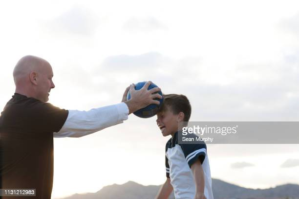 coach holding ball and boy heading it - heading the ball stock pictures, royalty-free photos & images