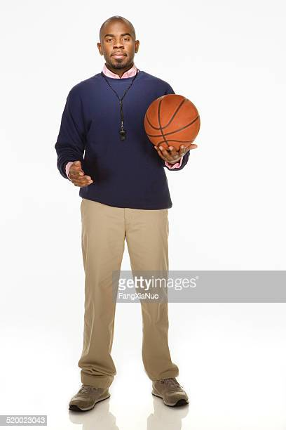 Coach holding basketball on white background, portrait