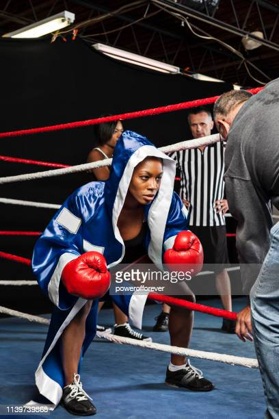 coach holding ropes open as woman boxer enters the ring - ducking stock pictures, royalty-free photos & images