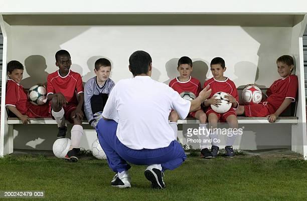 coach in front of football team of boys (8-12) sitting on bench - dugout fotografías e imágenes de stock