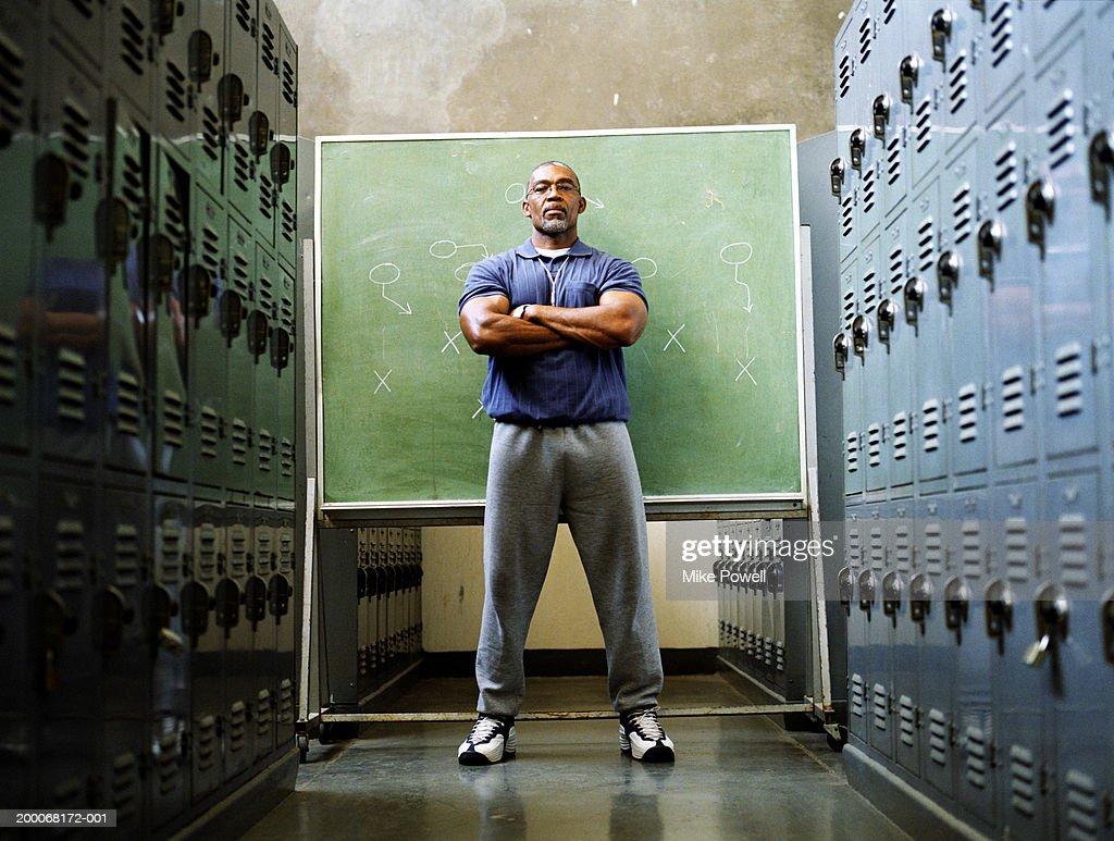 Coach in locker room, standing in front of chalkboard : Stock Photo