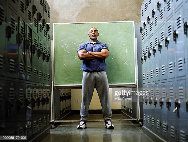 coach in locker room, standing in front of chalkboard - coach stock pictures, royalty-free photos & images