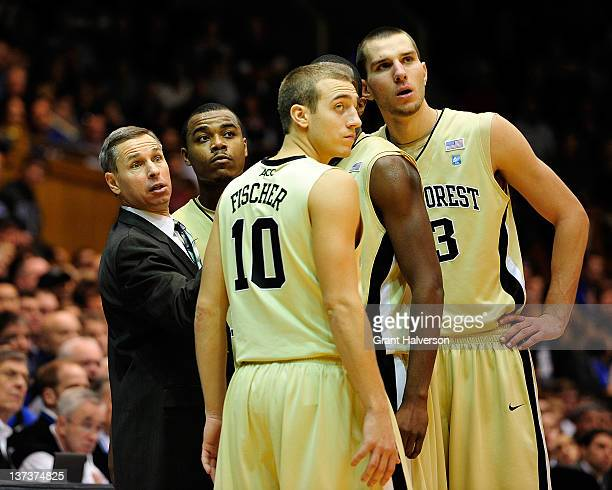 Coach Jeff Bzdelik huddles with Tony Chennault Chase Fischer and Carson Desrosiers of the Wake Forest Demon Deacons during play against the Duke Blue...