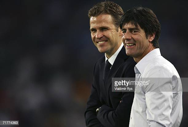 Coach Joachim Loew and team manager Oliver Bierhoff of Germany smile on prior to the Euro 2008 qualifying match between Germany and the Republic of...