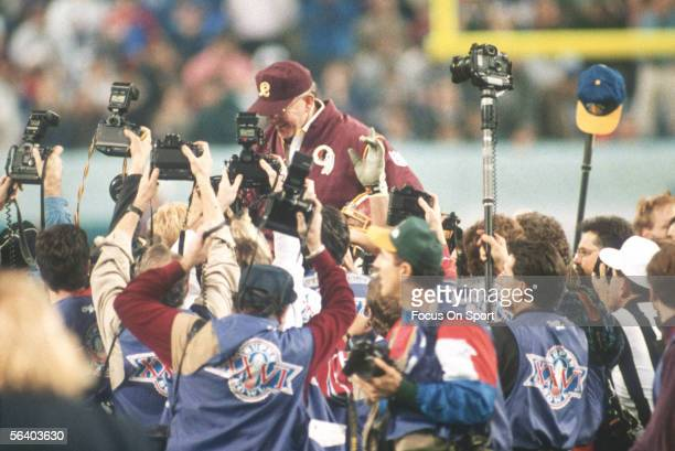 Coach Joe Gibbs of the Washington Redskins is held up by his teammates after winning the Super Bowl XXVI against the Buffalo Bills at the Metrodome...