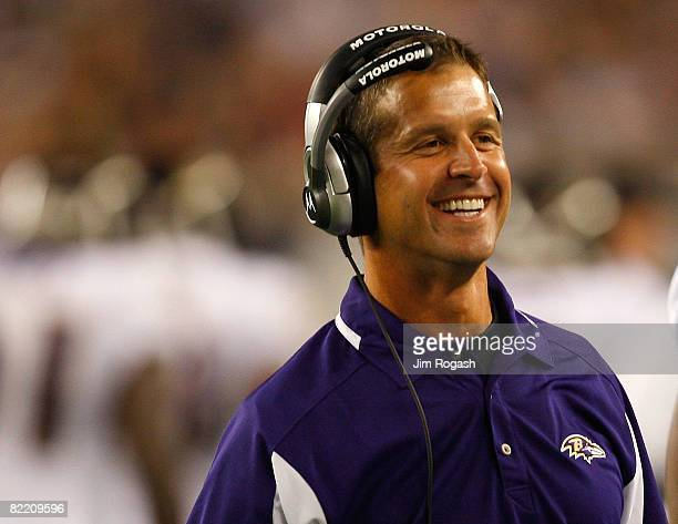 Coach John Harbaugh of the Baltimore Ravens smiles after a touchdown against the New England Patriots during a preseason game at Gillette Stadium on...