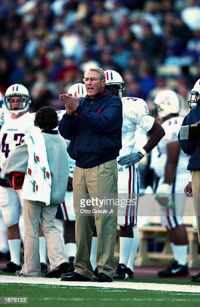 Coach John Mackovic of the Arizona Wildcats encourages his team from the sideline during the NCAA football game against the Washington Huskies at...