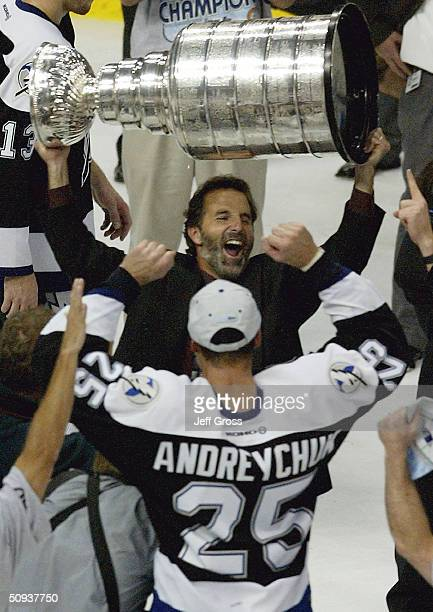 Coach John Tortorella of the Tampa Bay Lightning holds the Stanley Cup over his head while celebrating victory over the Calgary Flames with Dave...