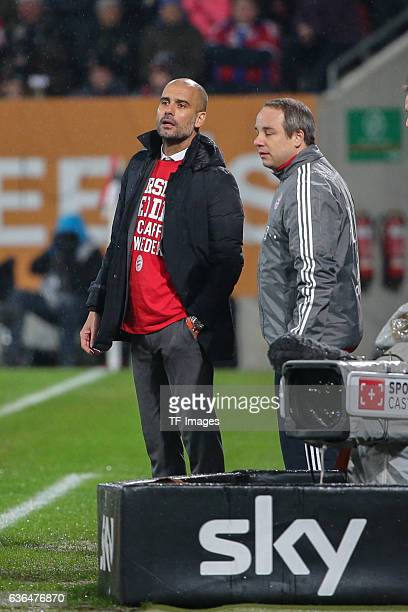 Coach Josep Guardiola of Bayern Muenchen and Doctor Dr Volker Braun of Bayern Muenchen looks on during the Bundesliga match between FC Augsburg and...