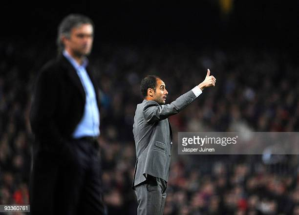 Coach Josep Guardiola of FC Barcelona gestures thumbs up to his players flanked by coach Jose Mourinho of Inter Milan during the UEFA Champions...