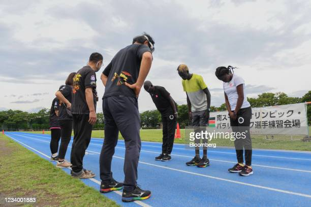 Coach Joseph Rensio Tobia Omirok, from third right, Akoon Akoon, and Lucia Moris, members of the South Sudanese track-and-field team, greet...