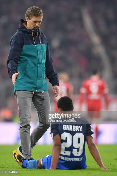 Coach Julian Nagelsmann of Hoffenheim walks over to Serge Gnabry of Hoffenheim who sits on the pitch dejected after the Bundesliga match between FC...