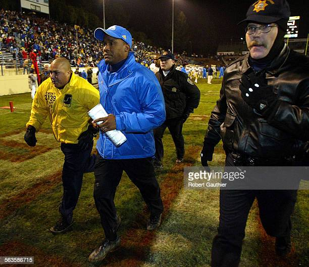 UCLA coach Karl Dorrell is escorted off the field after losing to Fresno State at the Silicon Valley Classic in San Jose Ca Tuesday December 30 2003