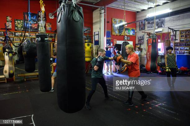 Coach Kelvyn Travis works with amateur boxers during a training session at the Moss Side Fire Station Boxing Club in Manchester, northwest England,...