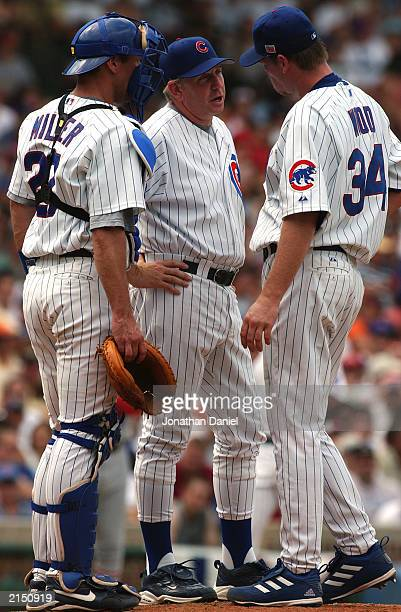 Coach Larry Rothschild and Catcher Damian Miller of the Chicago Cubs meet on the mound with pitcher Kerry Woods about his performance against the St...