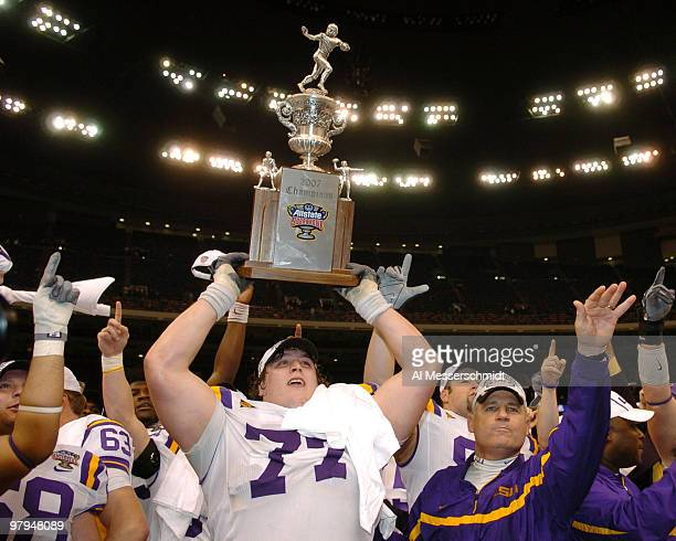 LSU coach Les Miles and offensive tackle Peter Dyakowski with the championship trophy after a win against Notre Dame in the Allstate Sugar Bowl at...