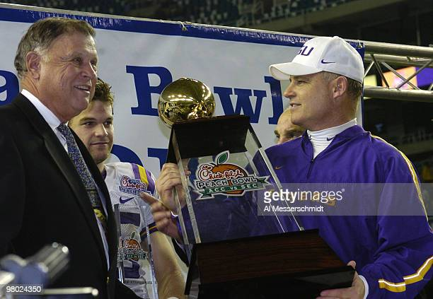 LSU coach Les Miles holds the championship trophy after defeating the University of Miami in the 2005 ChickfilA Peach Bowl at the Georgia Dome in...