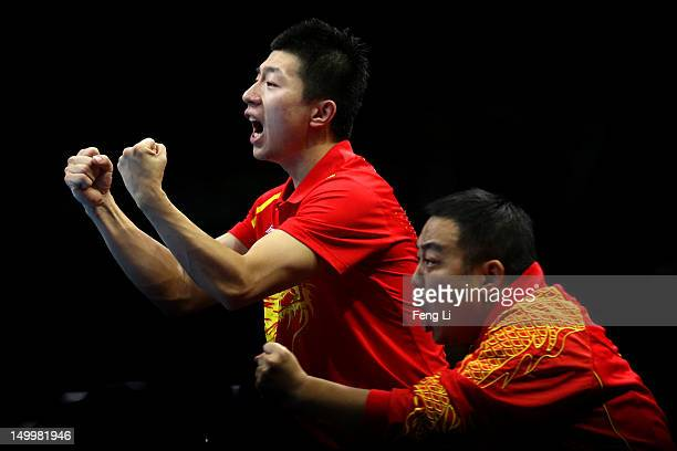 Coach Liu Guoliang cheers with Ma Long of China as Zhang Jike of China competes against Saehyuk Joo of Korea during the Men's Team Table Tennis gold...