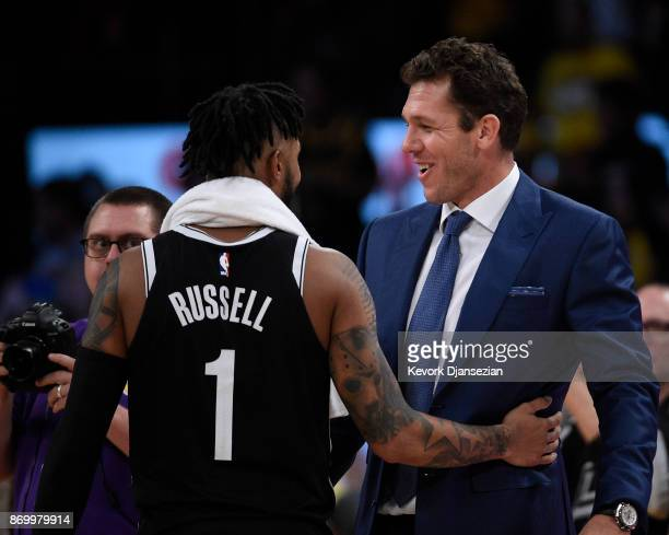 Coach Luke Walton of the Los Angeles Lakers hugs his former player D'Angelo Russell of the Brooklyn Nets who made his first come back to Staples...
