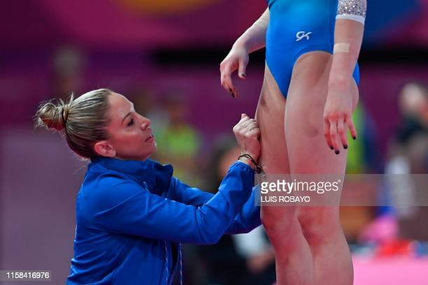 US coach Maggie Haney rub US Riley McCusker's legs before she competes in Floor during the Women's Individual AllAround Final event of the Lima 2019...
