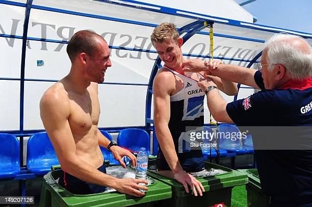 Coach Malcolm Arnold shares a joke with hurdlers Dai Greene and Jack Green as they take an ice bath after their training session during the Team GB...