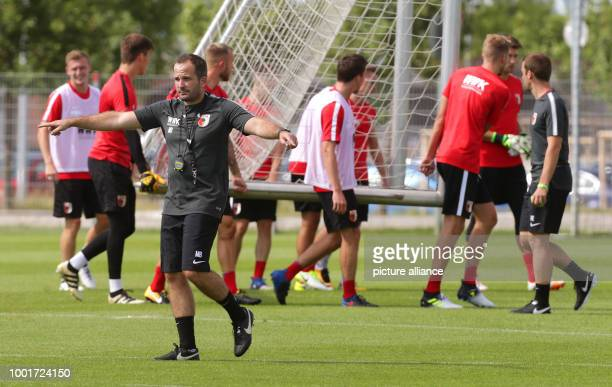 Coach Manuel Baum walks on the pitch in front of his players during the training start of German Bundesliga soccer club FCAugsburg in Augsburg,...