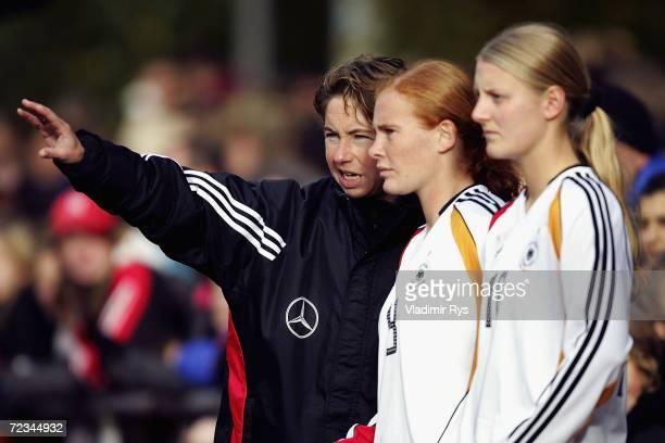 Coach Maren Meinert of Germany gives instructions to her players Christina Schellenberg and Marie Pollmann during the women's U19 international...