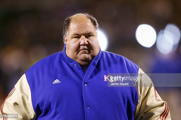 Coach Mark Mangino of the Kansas Jayhawks stands on the field with his team before the game against the Missouri Tigers at Arrowhead Stadium on...